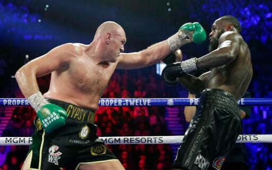 FILE - In this Feb. 22, 2020, file photo, Tyson Fury, left, of England, fights Deontay Wilder during a WBC heavyweight championship boxing match in Las Vegas. Fury is turning his attention to an all-British heavyweight unification bout with Anthony Joshua early next year after ending plans for a third fight with Deontay Wilder. Fury claimed the WBC belt from Wilder with a seventh-round stoppage in their rematch in Las Vegas in February and the British boxers U.S. promoter, Bob Arum, was looking to stage a third fight between them in front of 15,000 spectators at the home of NFL team Las Vegas Raiders on Dec. 19. (AP Photo/Isaac Brekken, File)