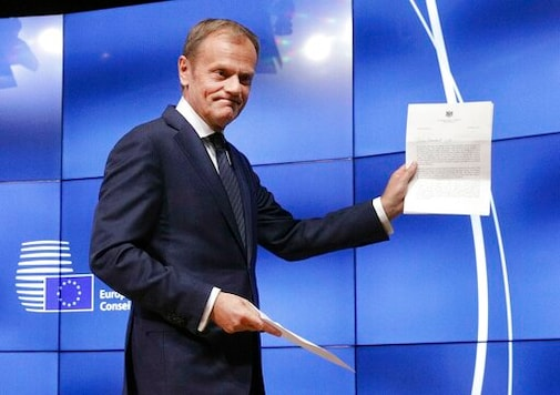 FILE- In this Wednesday, March 29, 2017 file photo, EU Council President Donald Tusk holds British Prime Minister Theresa May's Brexit letter in notice of the UK's intention to leave the bloc under Article 50 of the EU's Lisbon Treaty at a press conference in Brussels. (AP Photo/Olivier Matthys, File)
