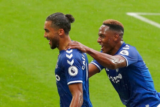Everton's Dominic Calvert-Lewin, left, celebrates after scoring his side's first goal during the English Premier League soccer match between Everton and Brighton at the Goodison Park stadium in Liverpool, England, Saturday, Oct. 3, 2020. (Peter Byrne/Pool via AP)