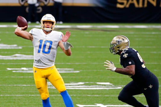 Los Angeles Chargers quarterback Justin Herbert (10) passes under pressure from New Orleans Saints defensive end Cameron Jordan (94) in the first half of an NFL football game in New Orleans, Monday, Oct. 12, 2020. (AP Photo/Butch Dill)