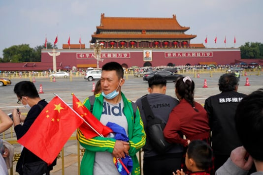 A tourists visiting Tiananmen Square holds Chinese national flags in Beijing on Thursday, Oct. 1, 2020. Some 637 million Chinese tourists took domestic trips during the 8-day long Golden Week holidays, spending billions as China looked to boost consumer-led spending to stimulate the economy. (AP Photo/Ng Han Guan)