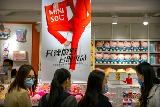 Customers wearing face masks to protect against the coronavirus browse at a Miniso shop at a shopping mall in Beijing, Thursday, Oct. 15, 2020.  Miniso, a Chinese discount retailer known for its fashionable but affordable household products, is expected to raise up to $562 million in a U.S. initial public offering in New York. The Guangzhou-based retailer is the latest Chinese company to list in the U.S., amid tensions that have taken U.S.-China relations to their worst level in decades. (AP Photo/Mark Schiefelbein)