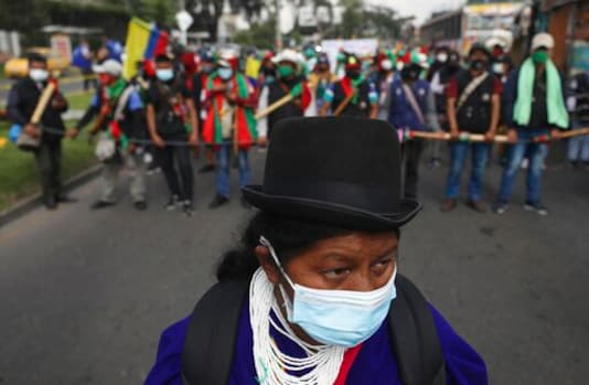 Members of the Indigenous Guard get ready to take part in an anti-government march in Bogota, where thousands traveled in a caravan from Cali, Colombia, Monday, Oct. 19, 2020. The leaders of the indigenous communities say they are mobilizing to reject massacres, assassinations of social leaders, criminalization of social protest, to defend their territory, democracy and peace, and plan to stay in the capital for a nationwide protest and strike on Oct. 21. (AP Photo/Fernando Vergara)