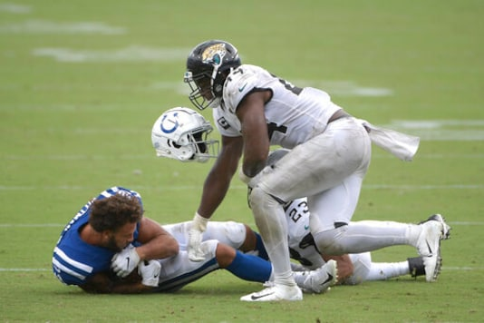 Indianapolis Colts wide receiver Michael Pittman loses his helmet after he was tackled by Jacksonville Jaguars middle linebacker Myles Jack and cornerback C.J. Henderson, back, during the second half of an NFL football game, Sunday, Sept. 13, 2020, in Jacksonville, Fla. (AP Photo/Phelan M. Ebenhack)