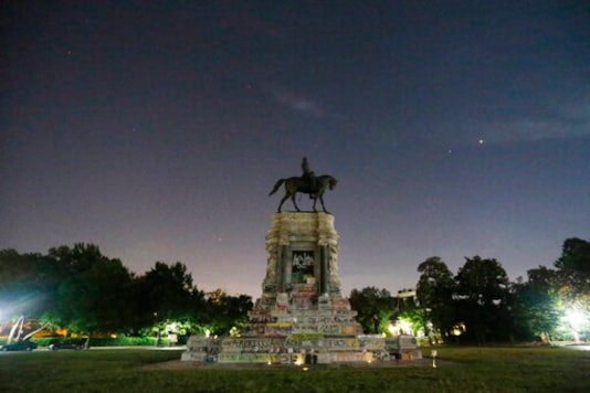 The moon and street lights illuminate the statue of Confederate General Robert E. Lee on Monument Avenue Friday June. 5, 2020, in Richmond, Va. A lawsuit seeking to prevent Virginia Gov. Ralph Northam from removing the statue is scheduled to go to trial Monday, Oct. 19, 2020. (AP Photo/Steve Helber)