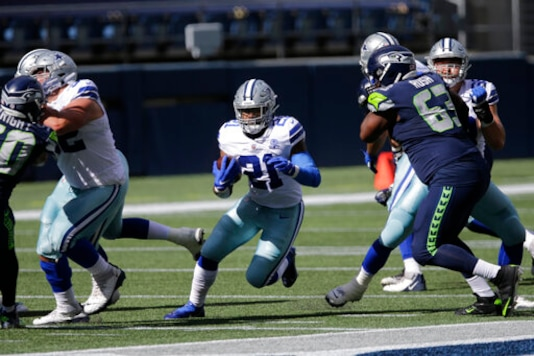 Dallas Cowboys running back Ezekiel Elliott (21) rushes against the Seattle Seahawks during the first half of an NFL football game, Sunday, Sept. 27, 2020, in Seattle. (AP Photo/John Froschauer)