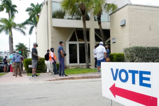 People wait in line to vote outside of an early voting site, Tuesday, Oct. 20, 2020, in Miami Beach, Fla. Florida began in-person early voting in much of the state Monday. With its 29 electoral votes, Florida is crucial to both candidates in order to win the White House. (AP Photo/Wilfredo Lee)