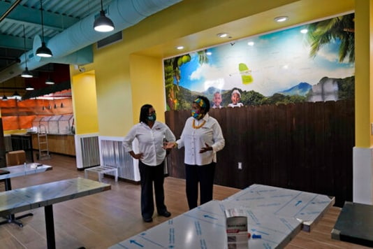 In this Aug. 26, 2020, photo Sophia Bramwell, left, and Antoinette Henry, right, talk at the soon to be opened Dutch Pot Jamaican Restaurant in Miami Gardens, Fla. Voters in the Democratic stronghold of Broward County are eager to defeat Trump, but say they are even more energized to turn out in support of California Sen. Kamala Harris, Bidens running mate whose father is Jamaican. The fact she has a lineage means you are going to see a lot of Jamaicans voting even if they were not doing so before, said Henry, Part of Jamaica will be in the White House. (AP Photo/Lynne Sladky)
