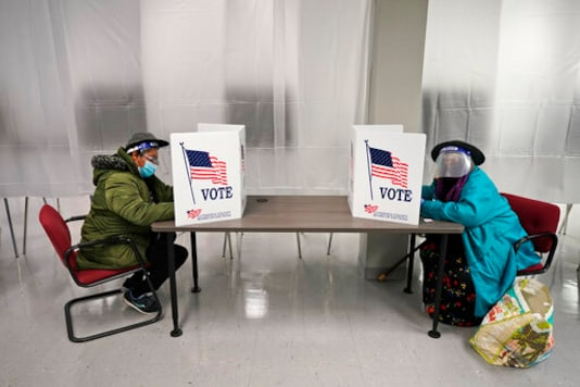 FILE - In this Oct. 6, 2020, file photo two voters fill out ballots during early voting at the Cuyahoga County Board of Elections in Cleveland. Hundreds of lawsuits about voting have been filed ahead of the November election.  (AP Photo/Tony Dejak, File)