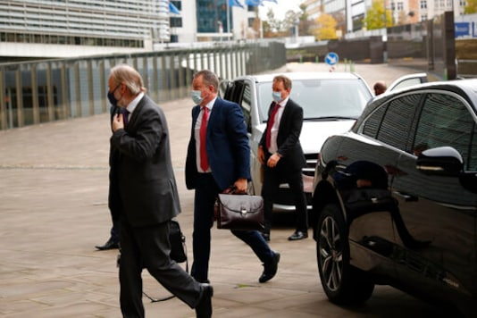 Britain's chief negotiator David Frost, center, and Britain's Permanent Representative to the EU Tim Barrow, left, arrive at EU headquarters for Brexit talks with EU chief negotiator Michel Barnier in Brussels, Wednesday, Oct. 14, 2020. (AP Photo/Francisco Seco)