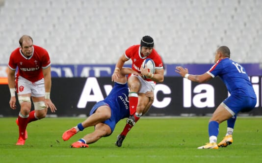 Leigh Halfpenny of Wales, center, is tackled during the rugby union international match between France and Wales at the Stade de France in Saint-Denis, near Paris, France, Saturday, Oct. 24, 2020. (AP Photo/Lewis Joly)