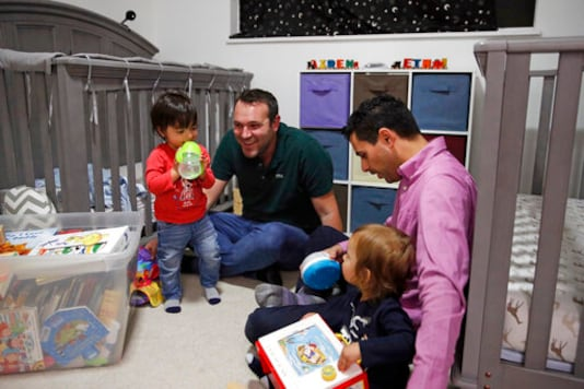 FILE - In this Jan. 23, 2020, file photo, Elad Dvash-Banks, right, and his partner Andrew, play with their twin sons, Ethan, left, and Aiden in their apartment in Los Angeles. A federal appeals court has ruled against the U.S. State Department in its quest to deny the citizenship of the son born abroad to the gay married couple. In a decision issued Oct. 9, 2020, the 9th U.S. Circuit Court of Appeals unanimously upheld a lower court ruling recognizing the citizenship from birth of Ethan Dvash-Banks, a twin boy born abroad by surrogacy to Andrew and Elad Dvash-Banks, a married gay couple. (AP Photo/Jae C. Hong, File)