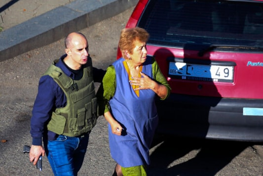 A Georgian police officer escorts a woman who escaped from a bank where an armed assailant has taken several people hostage, in the town of Zugdidi in western Georgia, Wednesday, Oct. 21, 2020. An armed assailant took several people hostage at a bank in the ex-Soviet nation of Georgia on Wednesday, authorities said. The Georgian Interior Ministry didn't immediately say how many people have been taken hostage in the town of Zugdidi in western Georgia, or what demands the assailant has made. Police sealed off the area and launched an operation