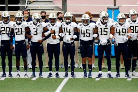 Georgia Tech players link arms before an NCAA college football game against Boston College as part of the Atlantic Coast Conference's first Unity Week, Saturday, Oct. 24, 2020, in Boston. (AP Photo/Michael Dwyer)