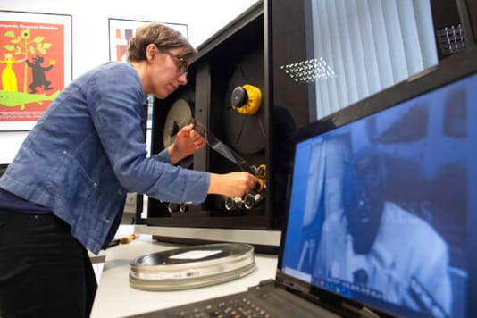 In this Wednesday, June 17, 2020 photo, archive employee Nora Freytag fixes a film roll for digitalization at PROGRESS Film, in Leipzig, Germany. A new project is underway to digitize thousands of East German newsreels, documentaries and feature films 30 years after Germanys reunification. The movies that are being scanned, transcribed and posted online provide a look inside a country that no longer exists but was a critical part of the Cold War. (AP Photo/Jens Meyer)