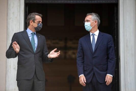 Greek Prime Minister Kyriakos Mitsotakis, left, welcomes NATO Secretary-General Jens Stoltenberg before their meeting in Athens on Tuesday, Oct. 6, 2020. (AP Photo/Petros Giannakouris)