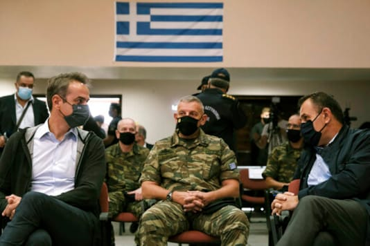 Greece's Prime Minister Kyriakos Mitsotakis, left, Greek Defense Minister Nikos Panagiotopoulos, right, and Armed Forces chief Lt. Gen. Konstantinos Floros, attend a presentation of the proposed construction of a new part of a fence which will be built at the border with Turkey, in Alexandroupolis, northern Greece, Saturday, Oct. 17, 2020. Greece decided to strengthen its land border with Turkey after the latter attempted to steer tens of thousands of migrant across into Greece last March. (Dimitris Papamitsos/Greek Prime Minister's Office via AP)