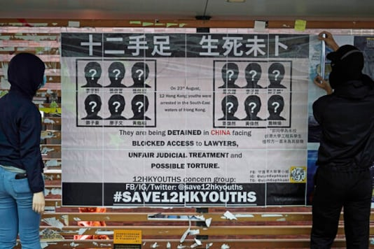 In this Tuesday, Sept. 29, 2020 photo, university students put up posters to demand of releasing the 12 Hong Kong activists detained at sea by Chinese authorities, at a