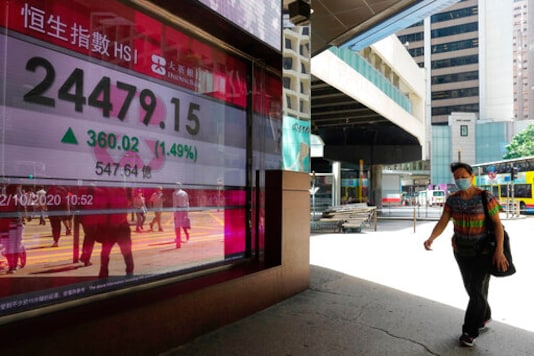 A man walks past a bank's electronic board showing the Hong Kong share index at Hong Kong Stock Exchange Monday, Oct. 12, 2020. Asian shares are mostly higher in muted trading on Monday, as worries about the pandemic keep optimism in check, despite the rally that closed out last week on Wall Street. (AP Photo/Vincent Yu)