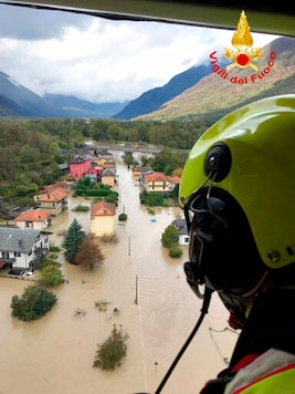 In this image made available Sunday, Oct. 4, 2020, firefighters fly over flooding in the town of Ornavasso, in the northern Italian region of Piedmont. (Firefighter Vigili del Fuoco via AP)