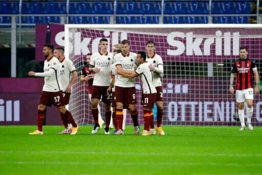 Roma's Edin Dzeko, center, celebrates after scoring his side's opening goal during the Serie A soccer match between AC Milan and Roma at the Milan San Siro Stadium, Italy, Monday, Oct. 26, 2020. (AP Photo/Luca Bruno)