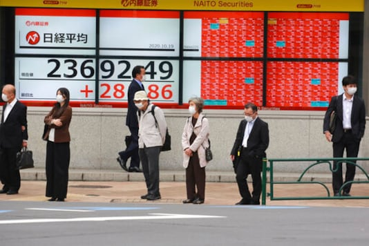 People stand by an electronic stock board of a securities firm in Tokyo, Monday, Oct. 19, 2020. Shares advanced in Asia on Monday after China reported its economy grew at a 4.9% annual pace in the last quarter, with consumer spending and industrial production rising to pre-pandemic levels. (AP Photo/Koji Sasahara)