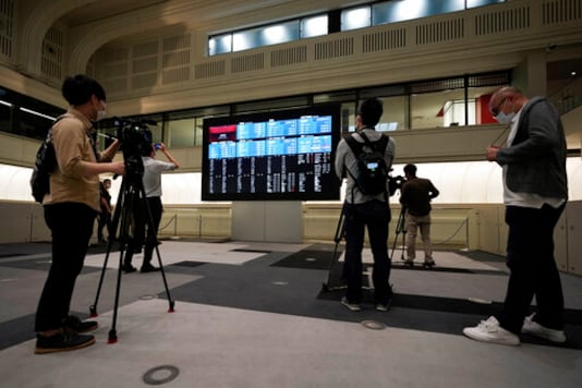 Members of media film the blank stock board at Tokyo Stock Exchange Thursday, Oct. 1, 2020, in Tokyo. The Tokyo Stock Exchange temporarily suspended all trading due to system problem. (AP Photo/Eugene Hoshiko)