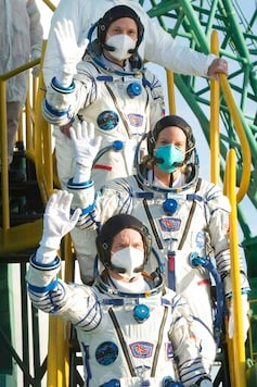 In this handout photo released by Roscosmos Space Agency, NASA's Kate Rubins, center, Sergey Ryzhikov and Sergey Kud-Sverchkov, top, of the Russian space agency wave before enter the Soyuz MS-17 for their trip to the International Space Station (ISS), at the Russian leased Baikonur cosmodrome, Kazakhstan, Wednesday, Oct. 14, 2020. A trio of space travelers has launched successfully to the International Spce Station, for the first time using a fast-track maneuver to reach the orbiting outpost in just three hours. (Andrey Shelepin/Roscosmos Space Agency via AP)