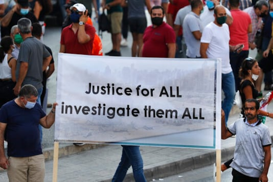 Lebanese supporters of President Michel Aoun, hold a banner during a protest calling for