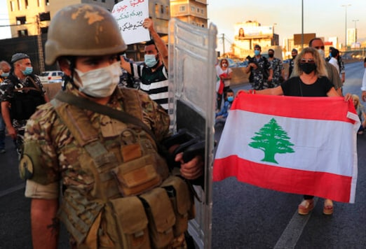 A Lebanese army soldier passes in front of an anti-government protester holding a national flag and blocking a main highway that links Beirut with north Lebanon during a protest against rising prices and worsening economic and financial conditions, in Zalka, north of Beirut, Lebanon, Monday, Oct. 5, 2020. Lebanon is passing through its worst economic and financial crisis in decades made worse by the coronavirus pandemic. (AP Photo/Hussein Malla)