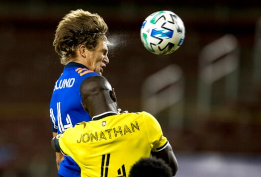 FC Cincinnati defender Nick Hagglund (14) heads a shot just over the goal as Columbus Crew defender Jonathan Mensah (4) guards him in the first half of an MLS soccer match Wednesday, Oct. 14, 2020, in Cincinnati. (Albert Cesare/The Cincinnati Enquirer via AP)