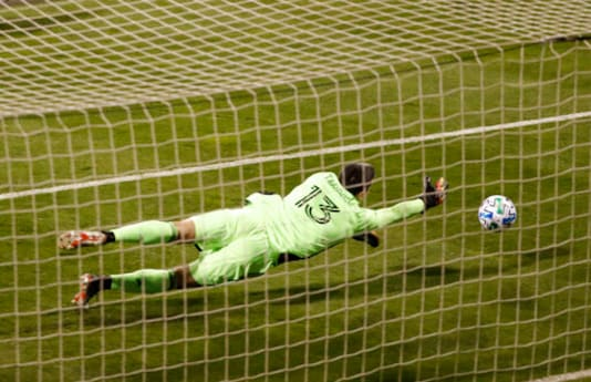 Columbus Crewgoalkeeper Andrew Tarbell dives to the right as a Montreal Impact shot gets past, but hits the post during the first half of an MLS soccer match in Columbus, Ohio, Wednesday, Oct. 7, 2020. (Kyle Robertson/The Columbus Dispatch via AP)