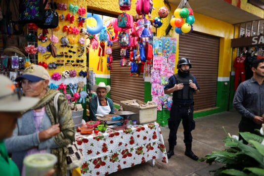 FILE - In this Feb. 10, 2020 file photo, a policeman stands guard as the city mayor attends an event to inaugurate renovated sections of the market, which, along with other local businesses, has suffered as violence has kept regional shoppers away in Apaseo El Alto, Guanajuato state, Mexico. The two most powerful drug cartels in the hemisphere are battling over this industrial and farming hub of central Mexico  a state that has attracted gangs for the same reason it has lured auto manufacturers: road and rail networks that lead straight to the U.S. border. (AP Photo/Rebecca Blackwell, File)