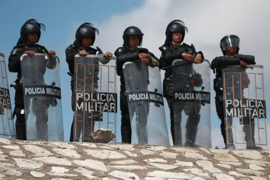 National Guard troops equipped with riot gear stand guard at Las Pilas dam, two days after withdrawing from the nearby Boquilla dam after clashing with hundreds of farmers, in Camargo, Chihuahua State, Mexico, Thursday, Sept. 10, 2020. President Andrs Manuel Lpez Obrador said Thursday he regretted the killing of a woman and the wounding of her husband following a Tuesday clash between National Guard troops and farmers over water. (AP Photo Christian Chavez)