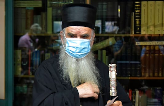 In this photo taken Sunday, Aug. 30, 2020, Serbian Orthodox bishop Amfilohije wearing a mask against the spread of the new coronavirus prepares to vote in parliamentary elections at a polling station in Cetinje, some 30 km south of Podgorica, Montenegro. The head of the Serbian Orthodox Church in Montenegro, which led months of protests against the small Balkan state's pro-Western government, has been hospitalized after testing positive for the coronavirus. (AP Photo/Risto Bozovic)
