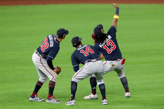 Atlanta Braves right fielder Ronald Acuna (13) takes a fake selfie with left fielder Nick Markakis, left, and center fielder Cristian Pache (14) after their win over the Los Angeles Dodgers in Game 2 Tuesday, Oct. 13, 2020, in the best-of-seven National League Championship Series at Globe Life Field in Arlington, Texas. (Curtis Compton/Atlanta Journal-Constitution via AP)