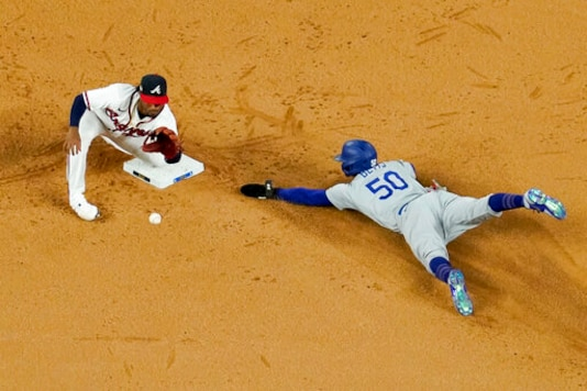Los Angeles Dodgers' Mookie Betts steals seconds past Atlanta Braves second baseman Ozzie Albies during the sixth inning in Game 5 of a baseball National League Championship Series Friday, Oct. 16, 2020, in Arlington, Texas. (AP Photo/David J. Phillip)