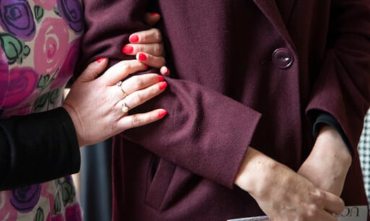 A supporter embraces the arm of New Zealand Prime Minister Jacinda Ardern, right, for a photo in central Christchurch, New Zealand, Wednesday, Oct. 14, 2020. Opinion polls indicate Ardern is on track to win a second term as prime minister in an election on Saturday. (AP Photo/Mark Baker)