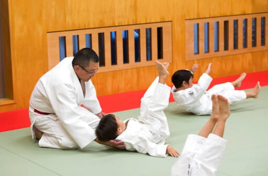 Judo teacher Tomoo Hamana helps protect the neck of a new student during a judo lesson at Hamana Dojo in Oiso town, west of Tokyo on Oct. 1, 2020. Japan is the home of judo, and the 19th-century martial art is sure to get more attention at home than any other sport at next years postponed Tokyo Olympics. But its also drawing unwanted scrutiny over widespread allegations of violence, and accompanying injuries and abuse. (AP Photo/Hiro Komae)