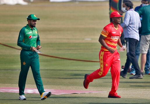 Zimbabwe's skipper Chamu Chibhabha, in red, and his Pakistani counterpart Babar Azam, left, walk back after the toss for their 1st one-day international cricket match at the Pindi Cricket Stadium, in Rawalpindi, Pakistan, Friday, Oct. 30, 2020. Pakistan won the toss and elected to bat first. (AP Photo/Anjum Naveed)