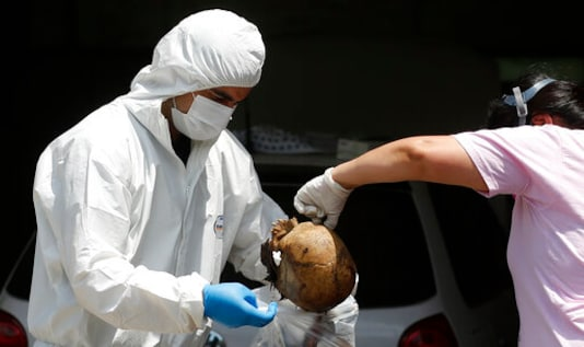 EDS NOTE: GRAPHIC CONTENT - Forensic police investigators hold a skull as they collect human remains from a container sitting in a street outside an office building in Asuncion, Paraguay, Friday, Oct. 23, 2020. According to prosecutor Marcelo Saldivar, seven bodies were found in the container, holding fertilizer, that left Serbia in July and arrived at Paraguay's Terport de Villeta port in October. (AP Photo/Jorge Saenz)
