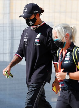 Mercedes driver Lewis Hamilton of Britain, left, walks near the track prior to the Formula One Portuguese Grand Prix at the Algarve International Circuit in Portimao, Portugal, Thursday, Oct. 22, 2020. The Formula One Portuguese Grand Prix will take place on Sunday. (AP Photo/Armando Franca)