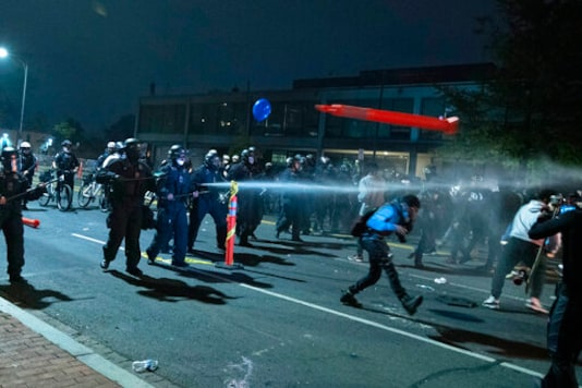 Washington Metropolitan Police Department police officers shoot pepper spray at demonstrators outside of the fourth district police station in Washington, Wednesday, Oct. 28, 2020. Demonstrators gathered at the police station in protest over a fatal a crash involving a moped driver who died when he police were attempting to pull him over. The crash happened last Friday. (AP Photo/Jose Luis Magana)