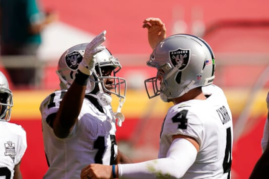Las Vegas Raiders wide receiver Nelson Agholor, left, celebrates with quarterback Derek Carr after catching a 59-yard touchdown pass during the first half of an NFL football game against the Kansas City Chiefs, Sunday, Oct. 11, 2020, in Kansas City. (AP Photo/Charlie Riedel)