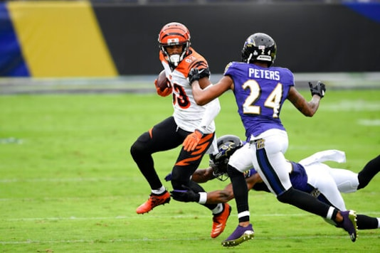 Cincinnati Bengals wide receiver Tyler Boyd (83) runs with the ball as Baltimore Ravens cornerback Marcus Peters (24) and cornerback Jimmy Smith (22) defend during the first half of an NFL football game, Sunday, Oct. 11, 2020, in Baltimore. In the midst of an NFL season that is on course to set records for the most points and touchdowns, the Baltimore Ravens and Pittsburgh Steelers are winning on the strength of their defense.(AP Photo/Nick Wass)