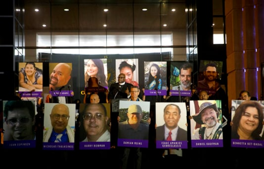 FILE - In this Dec. 7, 2015, file photo, San Bernardino County employees hold up photos of the San Bernardino shooting victims during a candlelight vigil in San Bernardino, Calif. Enrique Marquez Jr.,  who bought two rifles that a husband and wife used to kill 14 people in a California terror attack is expected to be sentenced.  He is scheduled to appear in federal court Friday, Oct. 23, 2020 in Riverside.   (AP Photo/Jae C. Hong, File)