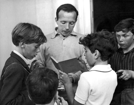 FILE - In this July 23, 1966 file photo, Nobby Stiles, the England soccer player, signs autographs for young fans outside the England team's hotel in Hendon, London. Stiles, a tenacious midfielder who won the World Cup with England in 1966 and the European Cup with Manchester United in 1968, has died. He was 78. Stiles' family said Friday, Oct. 30, 2020 that he died following a long illness.  (AP Photo/Peter Kemp, file)