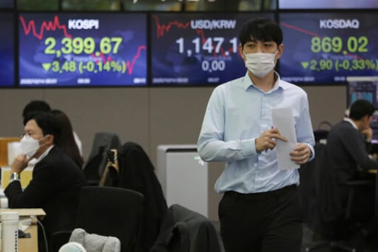 A currency trader walks with documents at the foreign exchange dealing room of the KEB Hana Bank headquarters in Seoul, South Korea, Wednesday, Oct. 14, 2020. Shares were mostly lower in Asia on Wednesday after pandemic concerns snapped a four-day winning streak on Wall Street. (AP Photo/Ahn Young-joon)