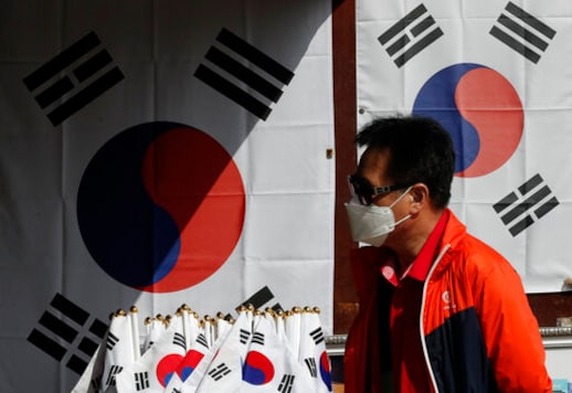 A man wearing a face mask walks near national flags displayed at a souvenir shop at the Imjingak Pavilion in Paju, South Korea, Sunday, Oct. 11, 2020. North Korean leader Kim Jong Un warned that his country would