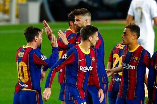 Barcelona players celebrate the opening goal of their team during the Champions League group G soccer match between FC Barcelona and Ferencvaros at the Camp Nou stadium in Barcelona, Spain, Tuesday, Oct. 20, 2020. (AP Photo/Joan Monfort)